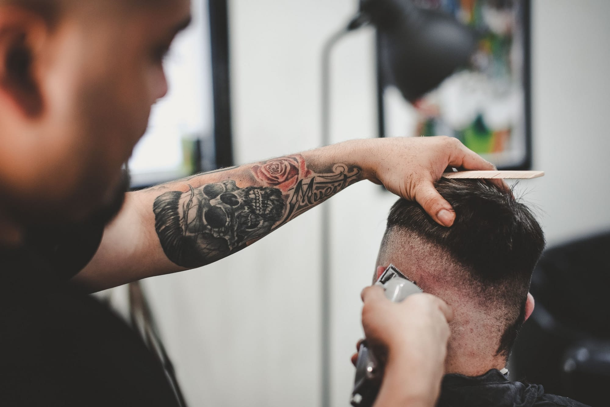 barber with tattoo cutting hair