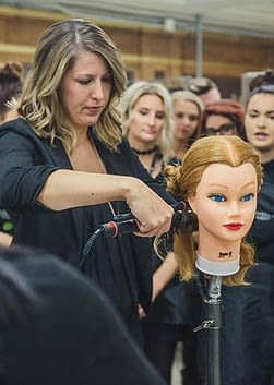 Student practicing their curling skills in the cosmetology program at Aveda Las Vegas