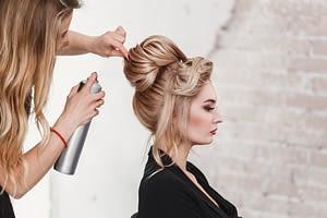 hairdresser styles a blonde woman's hair