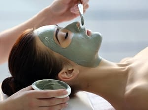 female spa client has mud face mask applied to her face