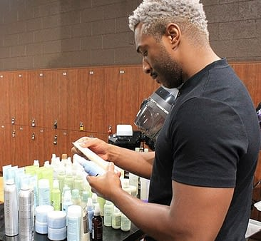 male esthetician student looking at Aveda skin care products