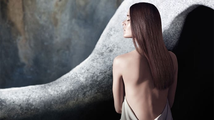 Aveda model with bare back witting in a natural setting