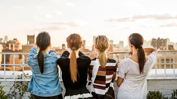 A line of women standing against a city sky line