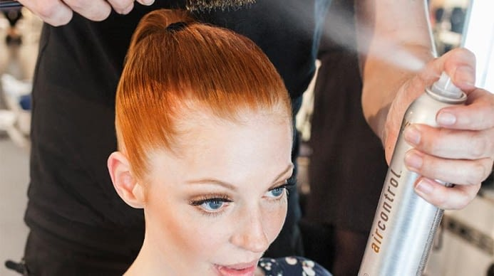 A red heard getting her hair pulled back into a pony tail. They are using Aveda AirControl spray