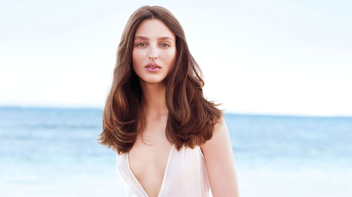 A beautiful brunette before the ocean wearing a plunged neck gown