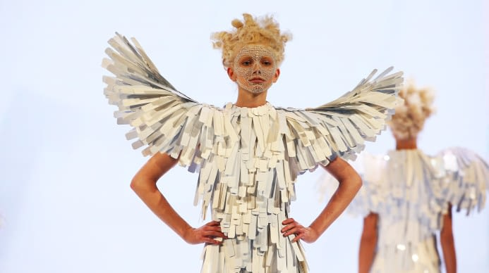 Woman designed to look like a bird with hair, makeup, and clothes adorned to match
