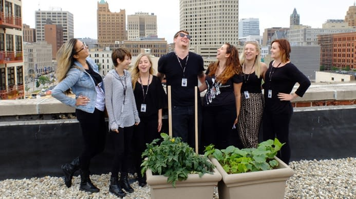 A group of Aveda students, in New York laughing at some garden boxes on a roof.
