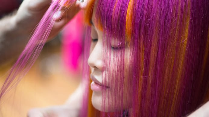 Woman with red and range hair getting her hair styled.