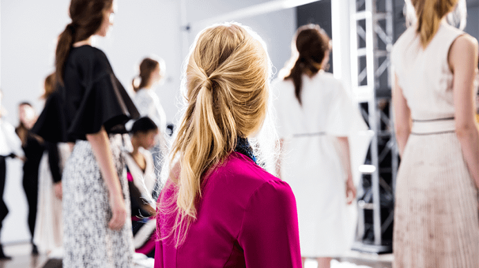 An aveda model from behind, her hair is pulled into a half ponytail
