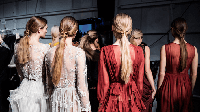 Four aveda models with their hair pulled into low knotted ponytails.