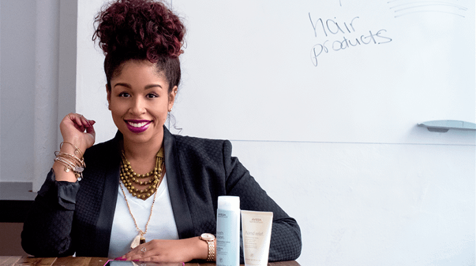 Woman with natural hair sitting with Aveda products