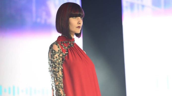 A woman in a red dress with a sharp purple lob cut