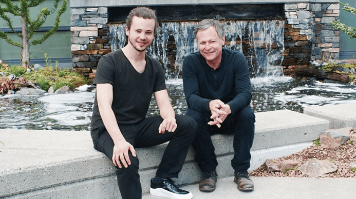 Two men sitting in front of a water fall