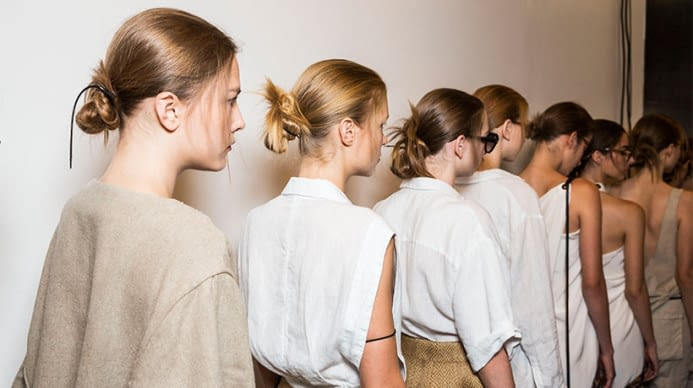 A line of Aveda models, dressed in white