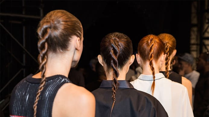 A line of Aveda models with the same twisted hair style