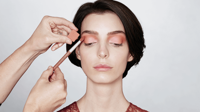 Dark haired woman getting natural makeup applied. Color swatch is displayed.