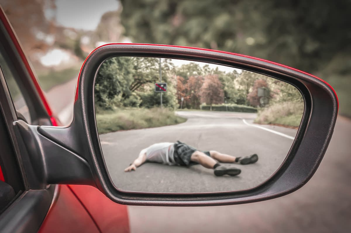 a man lying on the ground reflected in a rearview mirror