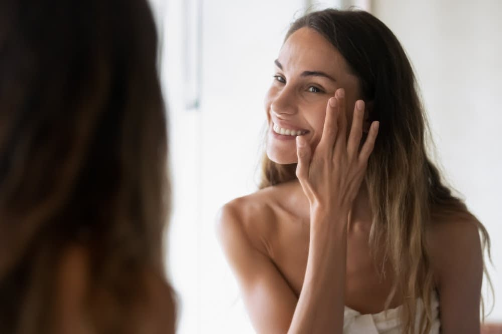 woman looking in the mirror and putting product on her skin