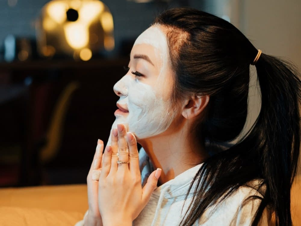 Woman applying a face mask at home.