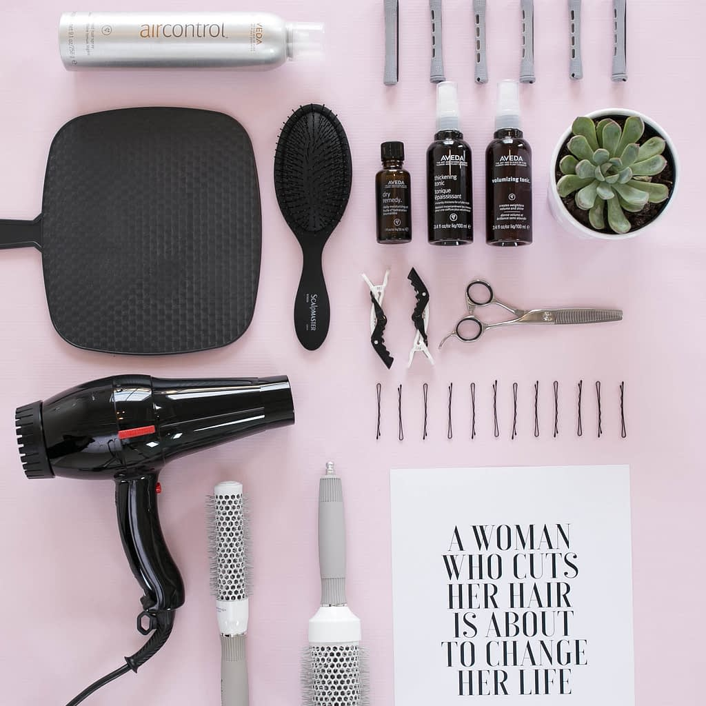 hair tools including a blow dryer, mirror, a brush, and more