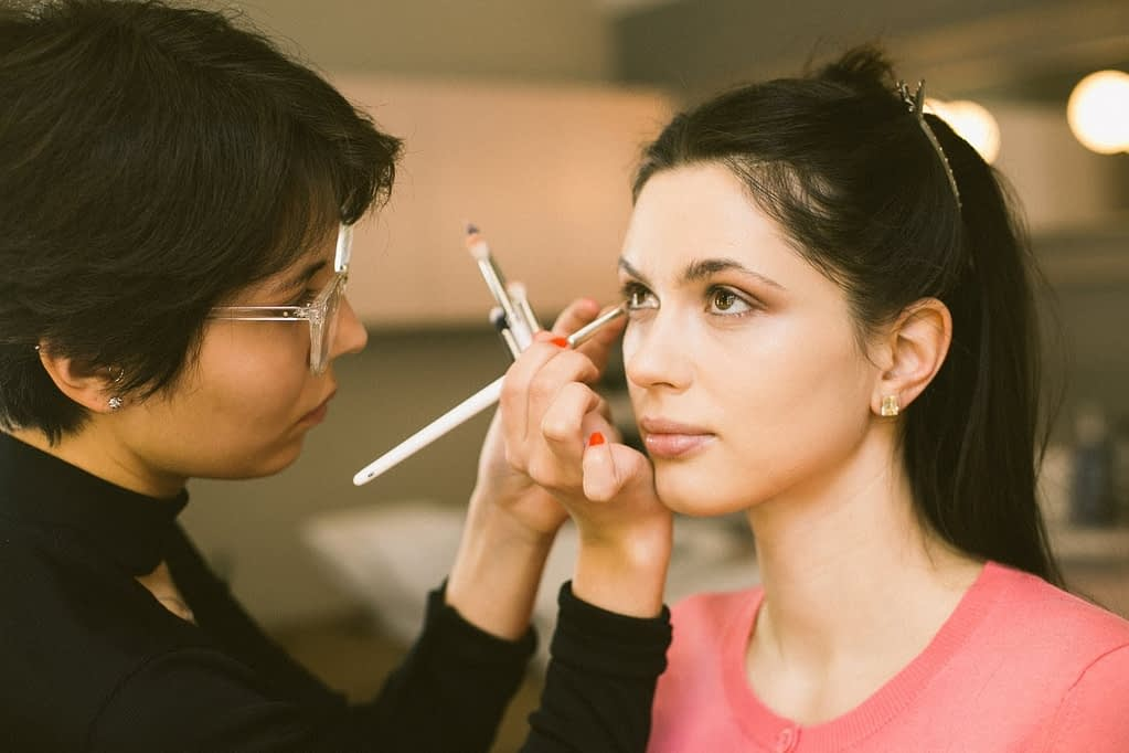black haired girl in pink tshirt getting her eyeliner done