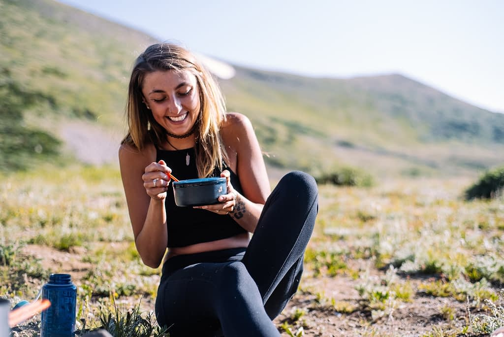 girl eating out of a bowl in wilderness