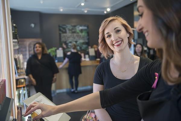 woman smiling in a beauty school salon