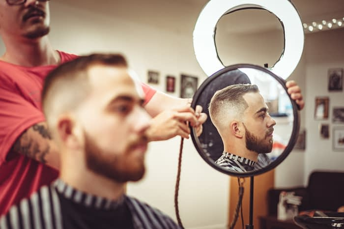 Barber holds up a mirror to his client.