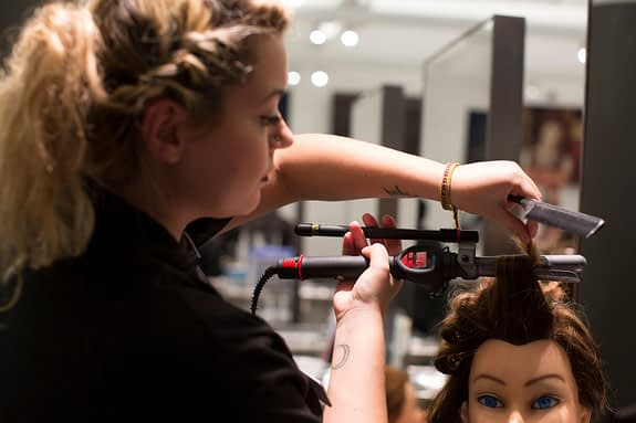 cosmetology student curling a mannequin head's hair