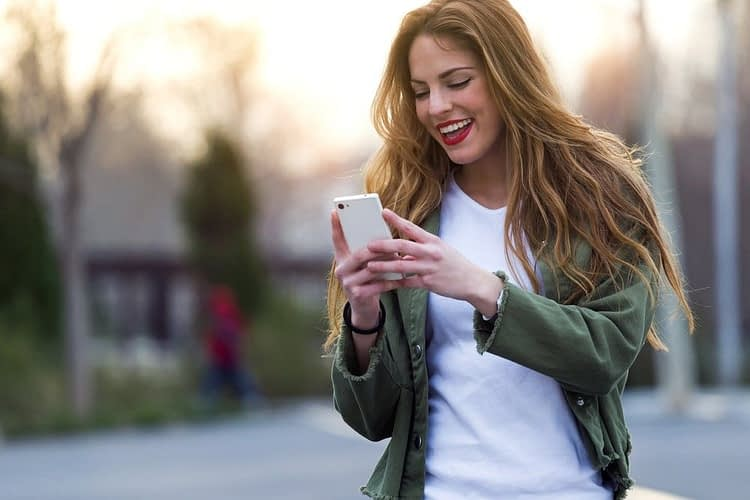 Woman looking at phone and laughing