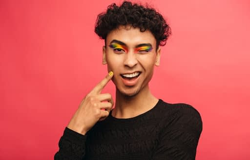 man with rainbow eyeshadow and smiling