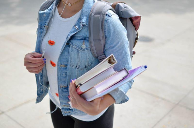girl holding textbooks for beauty school