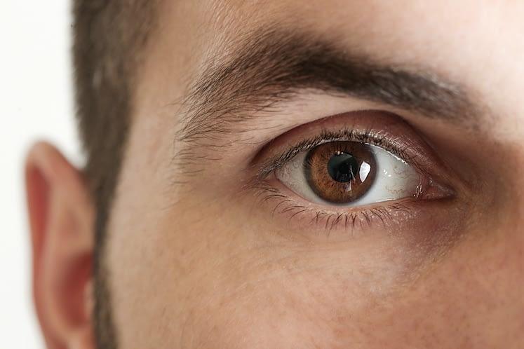 Close up view of a brown man eye looking at camera