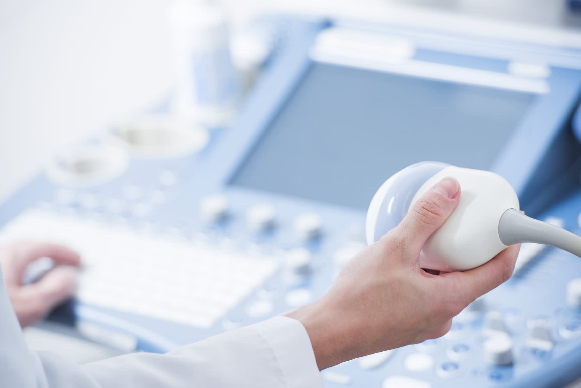 young woman doctor's hands close up preparing for an ultrasound device scan.