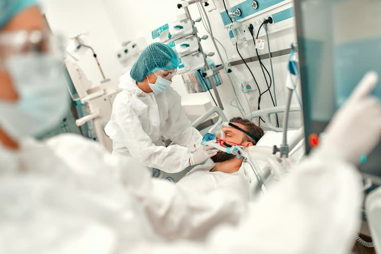 Doctors in protective suits put on a ventilation mask on a sick man with coronavirus disease covid-19, who is in an intensive care unit in a modern hospital.