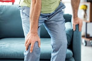 man clutching his knee in pain