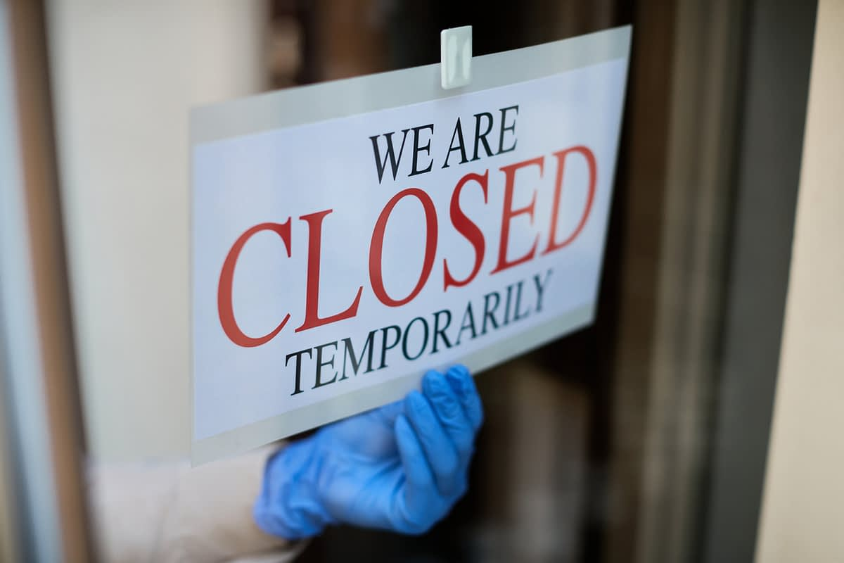 a gloved hand putting up a temporarily closed sign on a business door