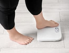 Woman Weighing Herself On Scale