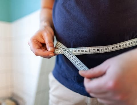 Man Measuring Waist To Monitor Weight Loss