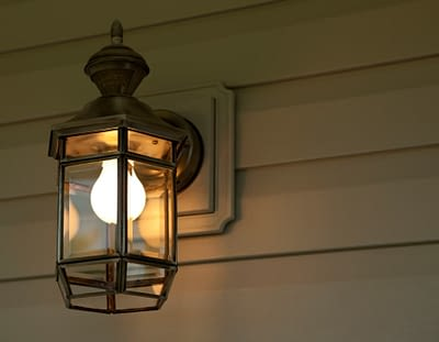 Wall Sconce On Vinyl Siding At Night