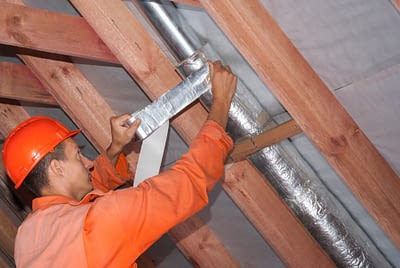 Man Repairing Duct In Attic