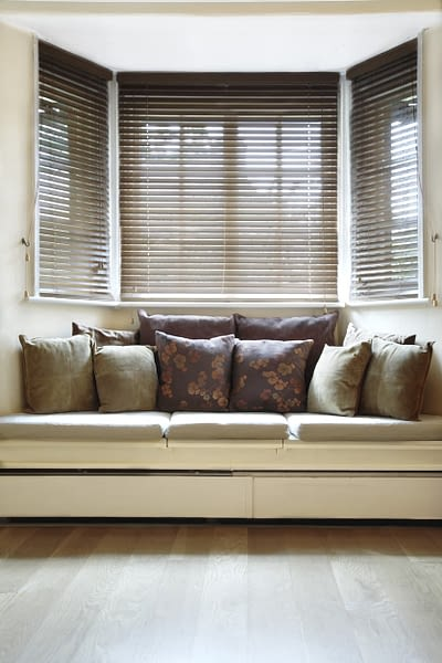 Bay window seat with pillows and blinds