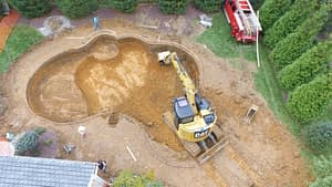 Backhoe in Excavation site for a new Custom Pool