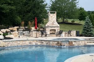 Outdoor fireplace by swimming pool