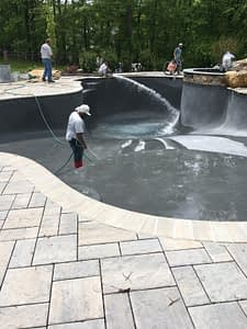 Men Filling Swimming Pool with Water