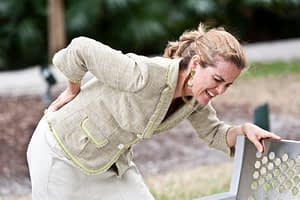 woman in park bent over with back pain