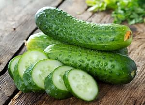 Cucumbers and slices on wooden table