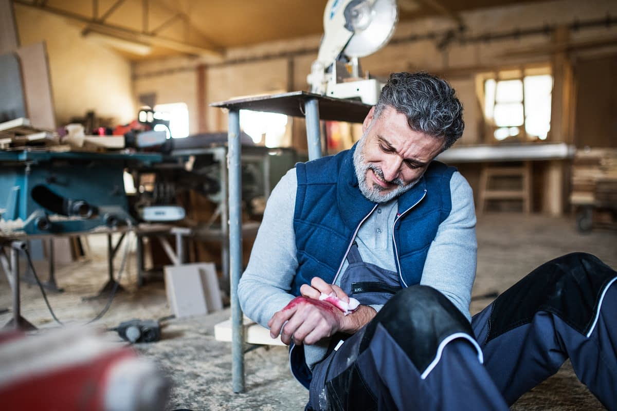 older man in workshop sitting on floor with injured hand