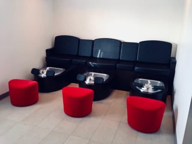 Pedicure stations with black leather seats and red foot stools