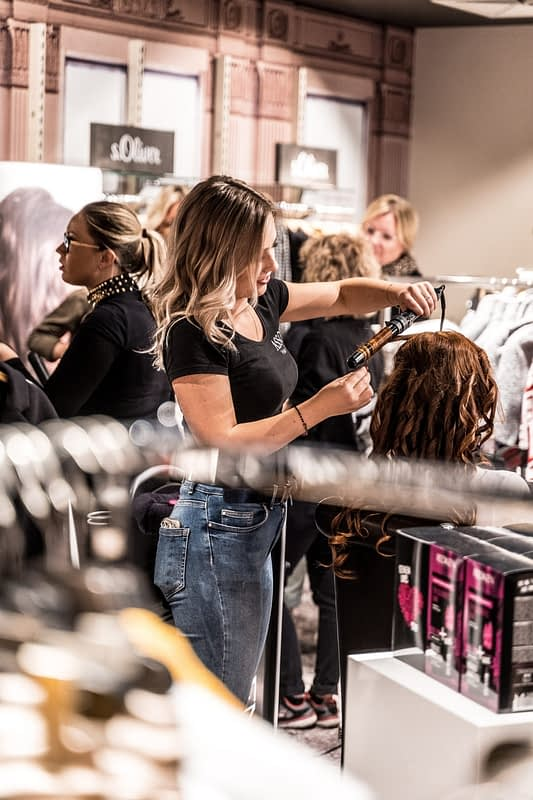 woman curling hair in a salon